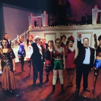 "the company singing ""Tomorrow belongs to Me"" with Jo Lloyd as Fraulein Kost"